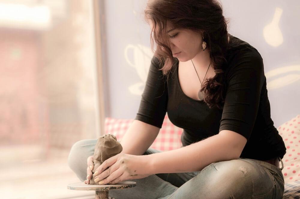 ろくろを回す陶芸家の女性の写真
