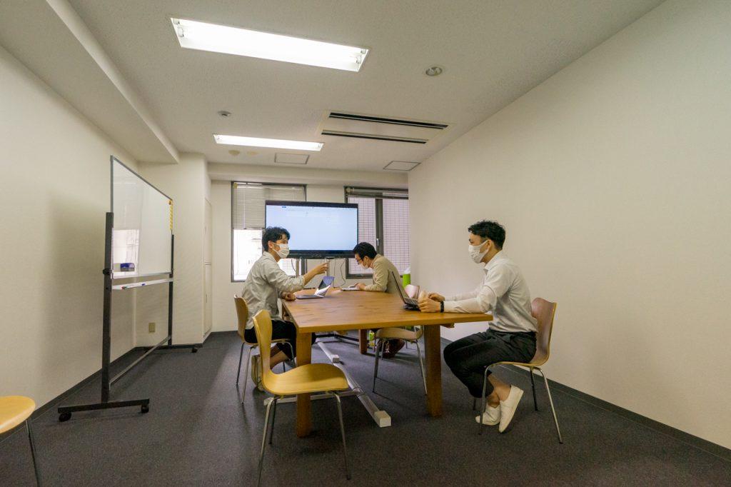 株式会社シェアウィズの大阪本社のミーティングスペースで会議している様子の写真